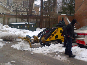 A skid steer snow pusher cleaning snow